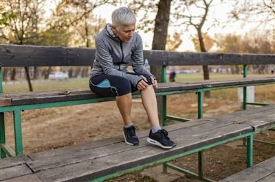 Person sitting down on bench inspecting leg