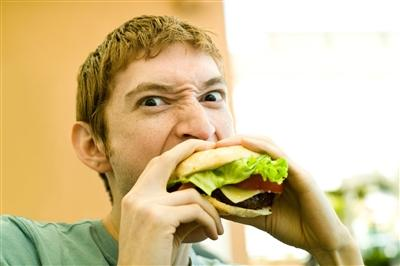 Man angry eating hamburger
