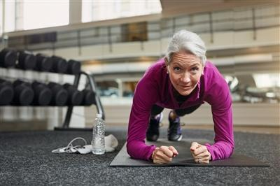 Older woman planking on yoga mat in gym