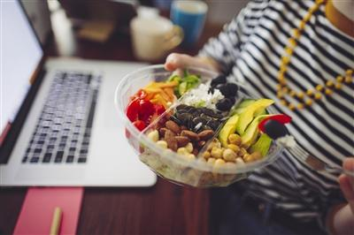 Close-up of person holding up a salad bowl while sitting at desk in front of laptop