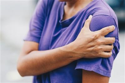 Woman clutching shoulder in pain