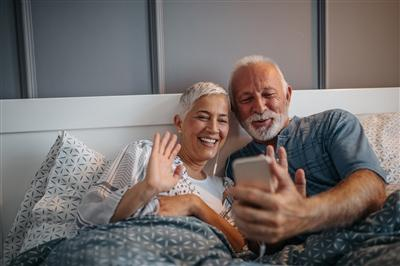 Older couple waving at phone on video chat with family