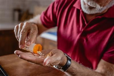 Man putting pills from pill bottle in hand