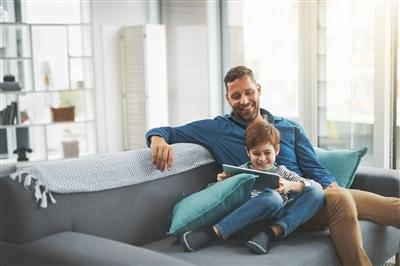 Father with son at home watching something on tablet