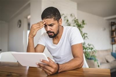 Worried man reading news on tablet