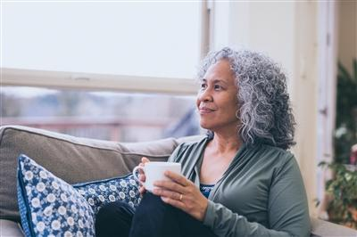Older woman holding coffee on couch looking out window