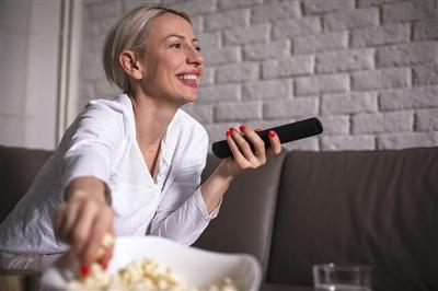 Woman on couch eating popcorn and watching TV