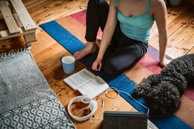 Woman on yoga mat surrounded by music pet and coffee