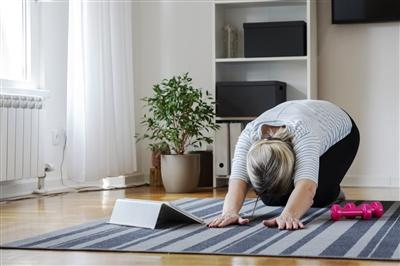 Senior woman following tutorial online and exercise at home