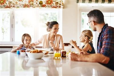 Family of four talking at breakfast table