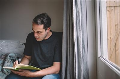 Man writing in journal at home near window