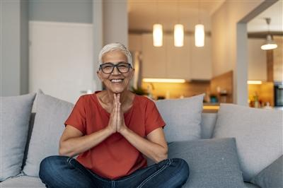 Mature female sitting cross legged at home smiling