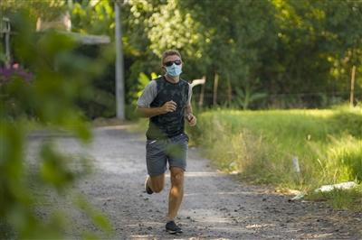 young attractive and happy man outdoors in city park doing running workout wearing protective face mask jogging and training