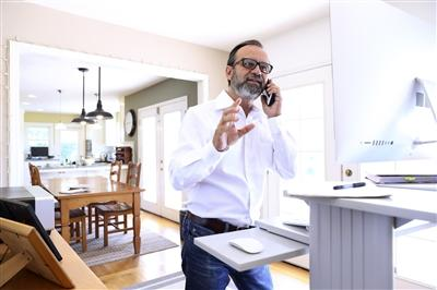 Businessman on the phone at home standing at standing desk