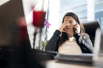 Woman sitting at desk showing physical symptoms of stress headache