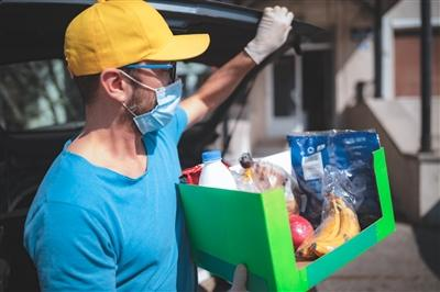 Man wearing mask and gloves and volunteering with food delivery