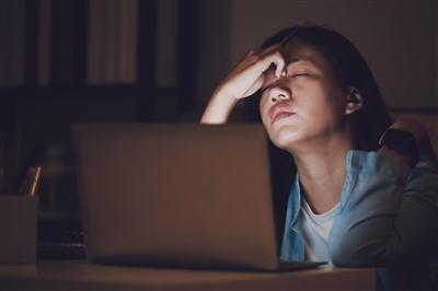 Woman in front of laptop with eyes closed and nose pinched between thumb and forefingers looking stressed