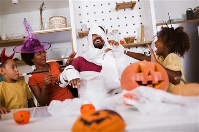 Parents and two young children dressing up and preparing for Halloween