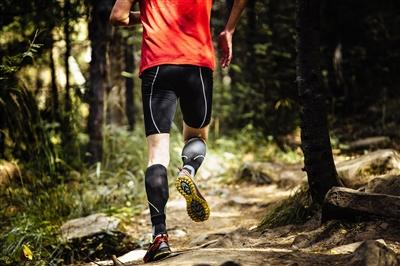 Runner in the forest wearing compression stockings on calves