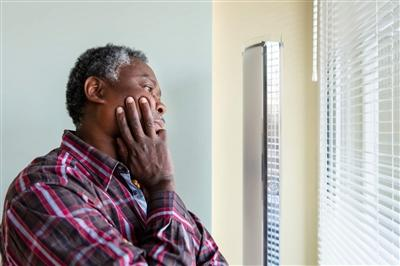 Older man in social isolation looking out window