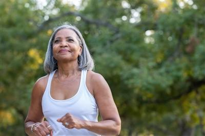 Senior woman jogging in park without headphones