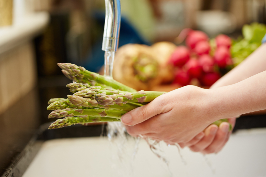 Close-up of female hands washing asparagus under faucet