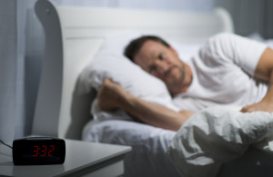 man laying in bed having trouble falling asleep