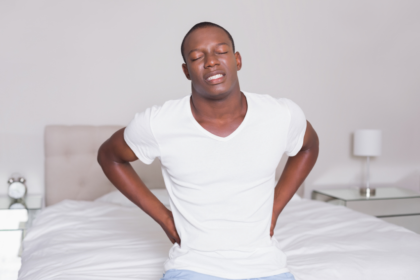 Wincing man sitting on the edge of his bed with a back ache at home in bedroom