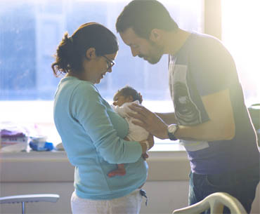 Mother holding newborn with father leans in over baby, all in hospital room