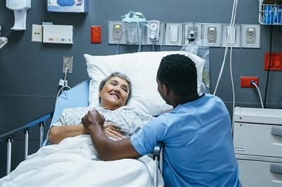 Nurse comforting smiling patient laying in hospital bed