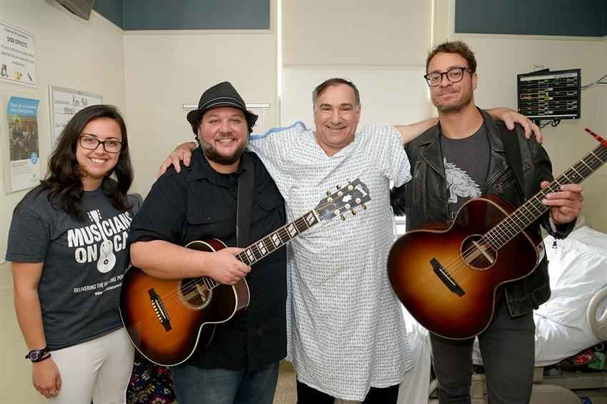 (Left to right) Kelli Bruno, manager of National Music Programs, Musicians On Call; Mutlu; John Novella, a patient at Bryn Mawr Hospital; and Amos Lee