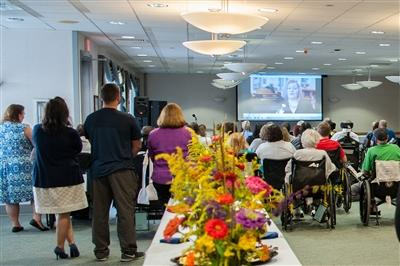 A room full of attendees watching the Bryn Mawr Rehab patient stories video