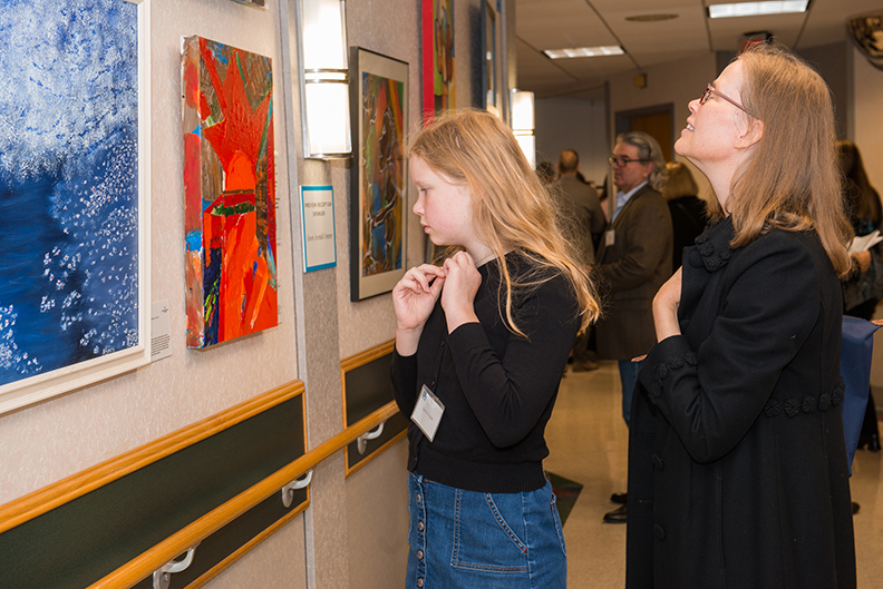 Visitors pause to observe the artistic stylings of a work and read about the artist's background at Art Ability