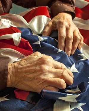 Older hands on an American flag