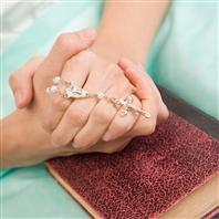 Hands folded over a bible holding a rosary