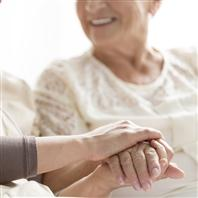 Caregiver holding hand of smiling patient
