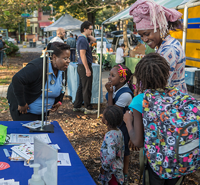 Flo, Main Line Health, talking with a mother and her children at a Clark Park event