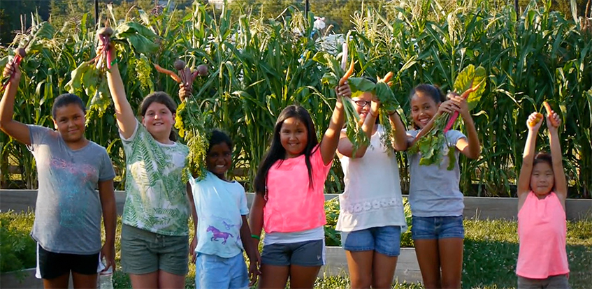 A group of girls holding up the carrots they harvested at the Deaver Wellness Farm