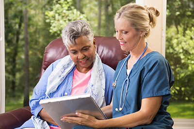 Health care provider and patient sitting looking at documents on a clipboard