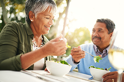 Man and woman enjoying eating salad at outside table