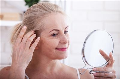 Woman looking at her face in a hand mirror
