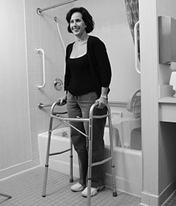 Demonstrating technique for getting out of a bathtub using bath seat