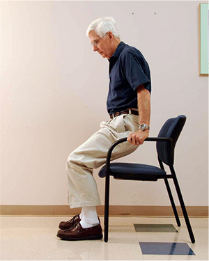 Demonstrating technique for getting out of a chair with arms