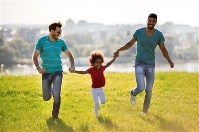 Two fathers and daughter running outside