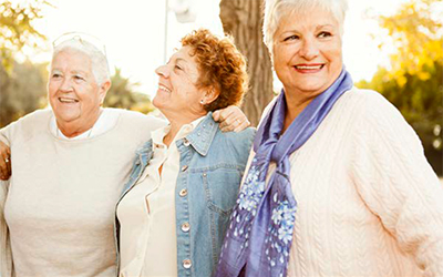 Three older woman smiling and enjoy outside