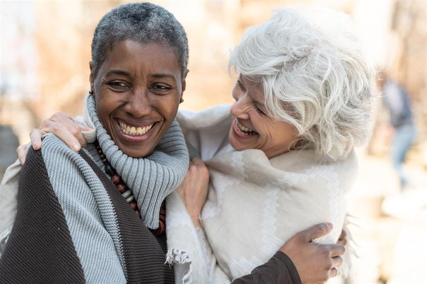 Two older women laughing and side hugging outside on a colder day
