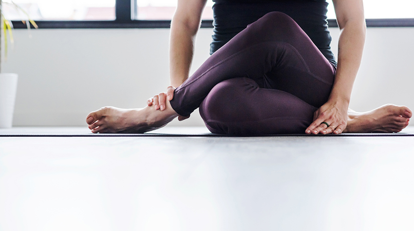 Close-up on middle-aged woman doing yoga indoors