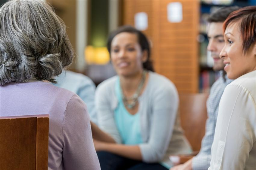 Unrecognizable woman shares story in group therapy