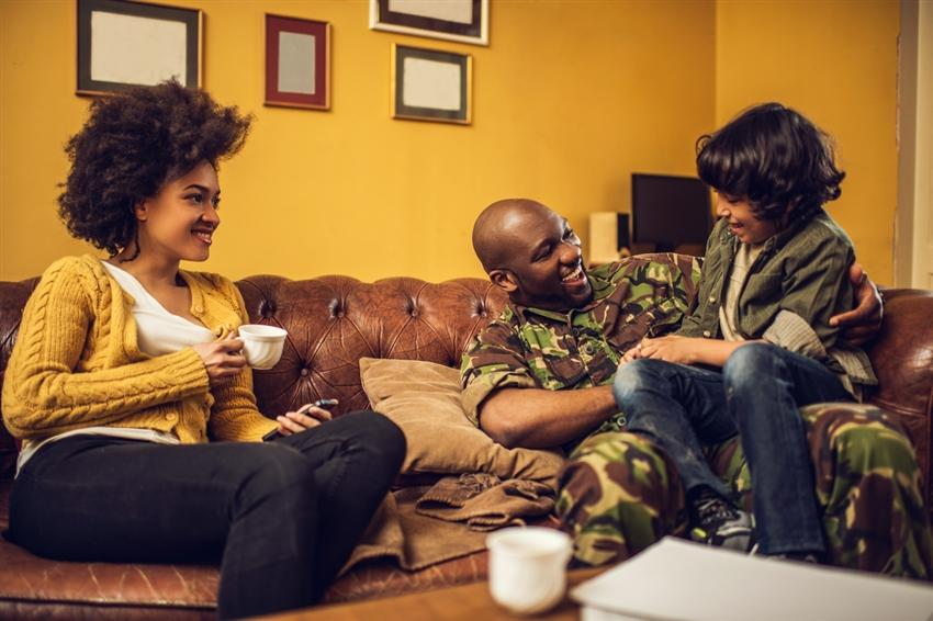 Cheerful African American military family having fun together at home