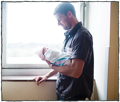 Father standing by window holding his newborn
